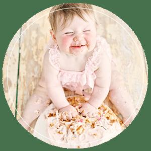 Smiling baby eating cake