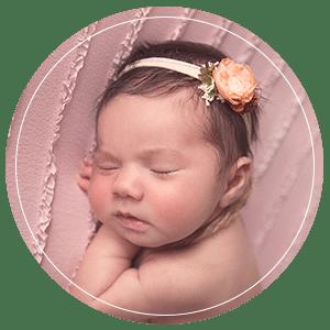 Newborn baby sleeping wearing a flower headband