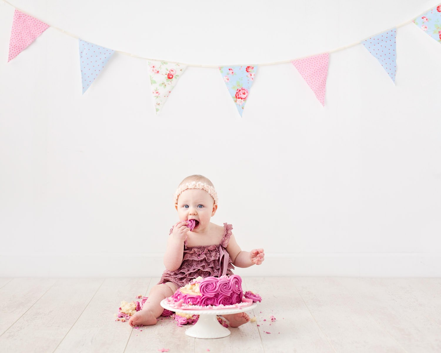 Girl eating cake in pink dress during cake smash photo shoot Glasgow