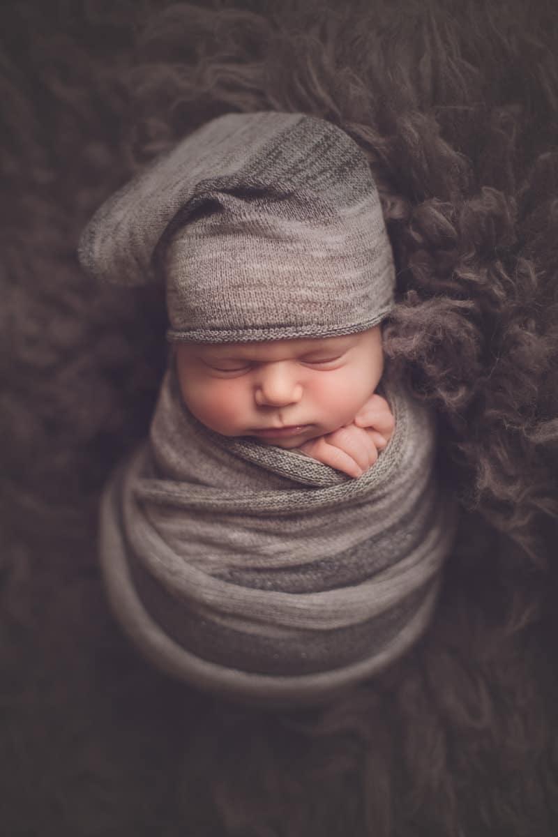 Newborn baby sleeping wrapped in grey blanket