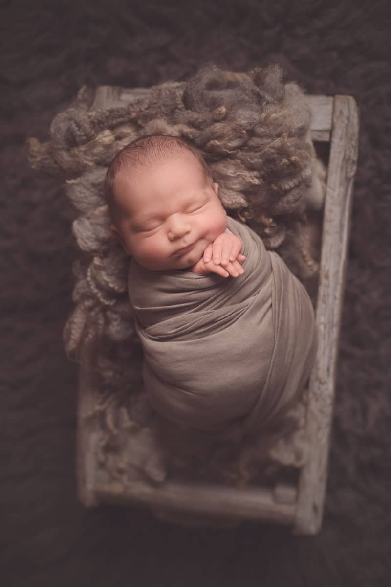 Baby swaddled in grey wrap during newborn photo shoot Glasgow