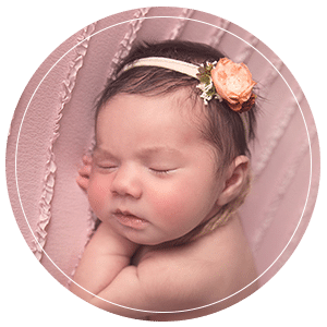 Newborn baby sleeping wearing a flower headband